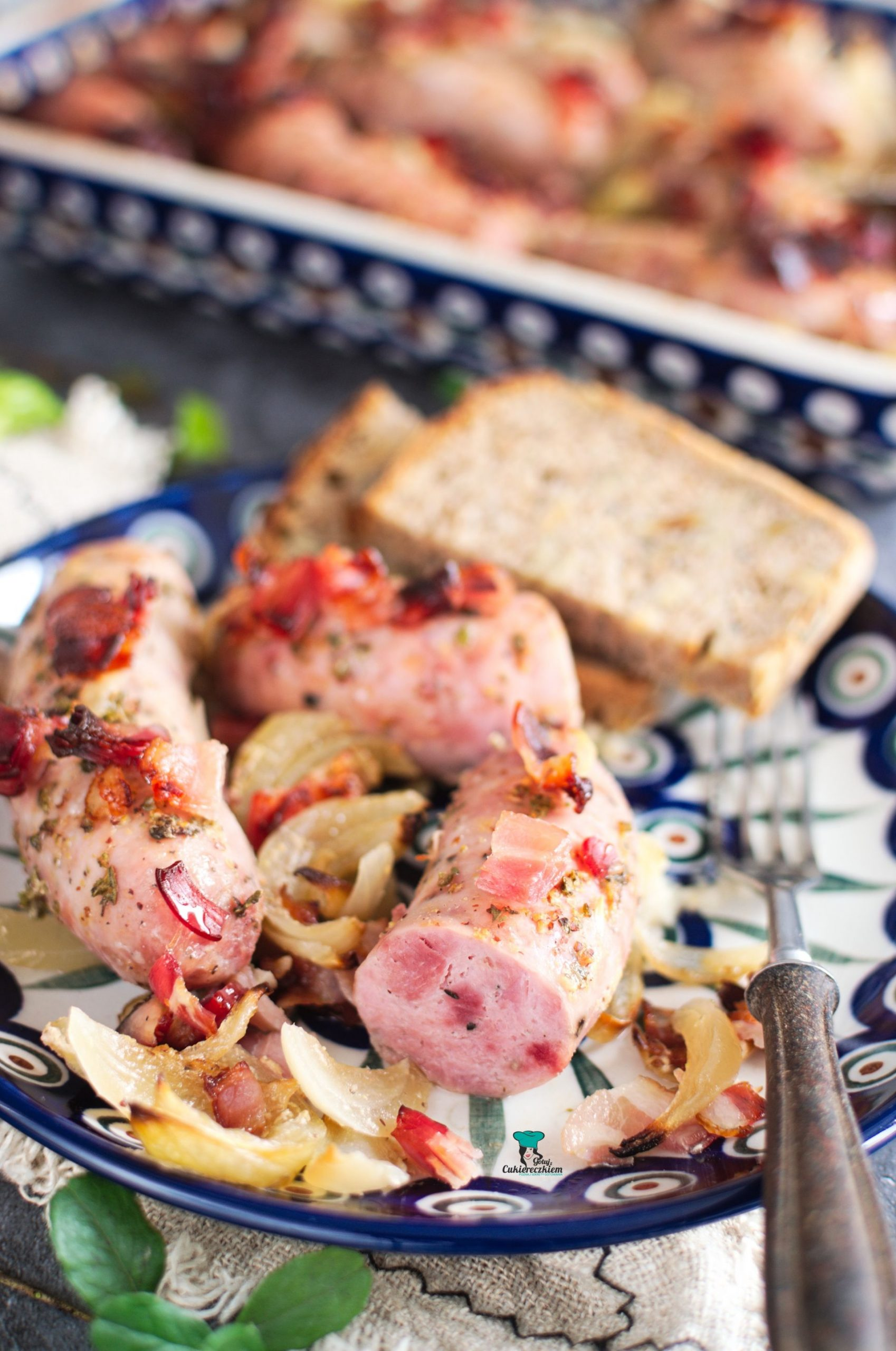 Biała kiełbasa pieczona z boczkiem i cebulą